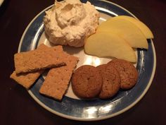 Fluffy pumpkin pie dip served on a plate with some apple slices, graham crackers, gingersnaps, and apple slices