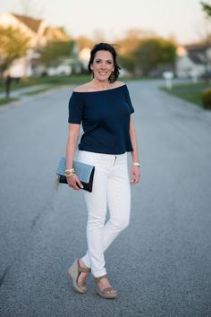 Jo-Lynne Shane styling a navy off the shoulder top with white jeans and wedge sandals.