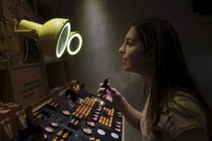 A woman checks lipstick applied on her lip, inside of a cosmetics shop in Sao Paulo, Brazil August 13, 2015. From cigarettes to lipstick to sandals, exports have emerged as a silver lining for Brazilian consumer goods companies that are suffering the worst domestic slump in over a decade. With Brazil's currency, the real, at a 12-year low, foreign sales have kept several companies in the black, helping them outperform rivals focused on the local market, according to a Reuters analysis of…