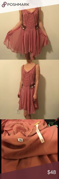 FREE PEOPLE Mauve Silk Beaded Trapeze Dress Gorgeous Free People Mauve pink Beaded dress with a floral Detail on the sides and has an asymmetrical bottom. A slip underneath comes along with it and it is a size extra small. Knee length and has a small tear in the front panel that may be able to be repaired. Reflected in price. Free People Dresses Midi