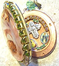 $99 SALE Oval locket with large Aurora borealis rhinestones above the large glass cameo depicting the Holy Family. Peridot green rhinestones on the sides and pink rhinestones along the bottom. Saint Joseph and the Virgin Mary with the Christ child. Inside is features the a Sacred heart of Jesus and Our Lady of Grace Miraculous medal, a four way cross with saint Anthony and St. Christopher and pink and green rhinestones on the right hand side.   The left side of the locket is for your
