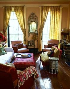 bohemian look living room with wide plank floors and gold drapes