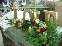 Love letters with greenery garland and spray roses.