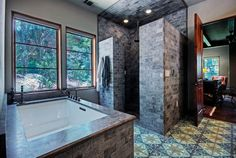 This Mediterranean bathroom brings nature in with a rich detail of stone brick tiles and a couple of panorama windows.Photo by Rick O'Donnell Architect