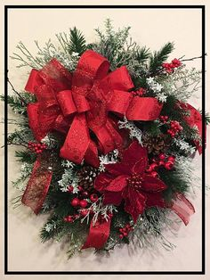 This is an elegant and classy Christmas wreath featuring a lovely red poinsettia, red joy and glitter ribbon, red pomegranates and berries, frosted cedar, pine cones with winter greens and fillers. It measures @ 28L x 24W x 8D and looks absolutely gorgeous above a fireplace or