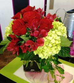 Custom centerpiece with red roses, red alstroemeria and green miniature hydrangea created for a concierge client.