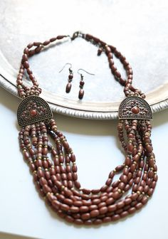 """Cocoa Bean Beaded Necklace 23.99 at shopruche.com. This statement necklace is accented with gold and brown beads and intricately detailed pendants. Includes with matching earrings.  13""""-14.75"""" length"""