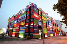 The brightly colored panels that clad the exterior of the Estonia Pavilion are dye-sub printed Ferrari Soltis® 86 mesh fabric, wrapped around steel frames and fastened on the back with flathead screws. Rainscreen Cladding, Metal Cladding, Tensile Structures, Concrete Facade, Fabric Structure, Colourful Buildings, Textiles, World's Fair, Arquitetura