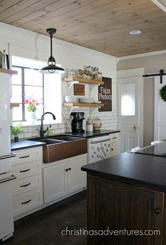 A beautiful apron front hammered copper sink is the focal point of this farmhouse kitchen. Love the subway tile, open shelving, white cabinets, and black granite countertops.