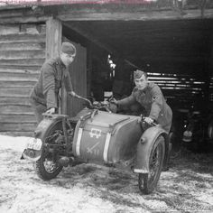 Soldiers removing their motorcycle from a shed during winter