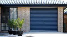 This is a cool garage door. I like the blue color on this roller door. I like how the blue contrasts with the tan brick. Its cool when a garage become the focal point.