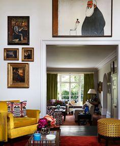 gold velvet chair, ikat pillow, cane-patterned ottoman, gold-framed art, art arrangement, green silk drapes, archway, eclectic traditional Katrin Bellinger: Master Collector