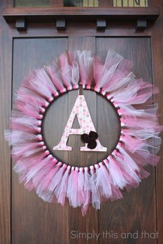 Simply This and that: Baby Girl Shower doesn't just have to be for a baby shower...Disney door decoration! Embroidery hoop, tulle/ribbon, glued magnets, and family monogram.