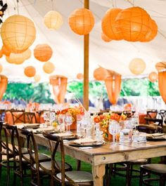 Orange paper lanterns in a tent, rustic table, long table for dining, varied centerpieces, orange wedding theme