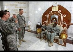 In 2009, U.S. soldiers take souvenir photos with a chair that belonged to Saddam Hussein at the former presidential palace.