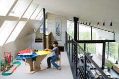 The loft above the living room is Suresh's terrain, given over to toys, books, and a colorful Lego table. The Clerestory windows maximize the natural light in the house—essential since there are only three hours of sun on a typical winter day. Photo by: Erik Johnson   Dwell