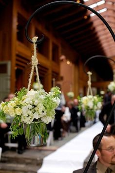 At a rustic chic wedding, floral arrangements suspended with twine hang from wrought iron hooks ~ https://www.insideweddings.com/weddings/rustic-spring-wedding-in-southern-california/454/