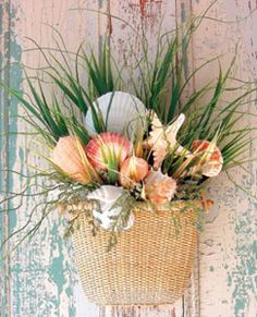 Very attractive arrangement of shells and grass in a wall basket. this says welcome summer...something i like to celbrate with my grandkids especially