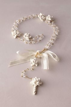 A beautiful keepsake gift for her First Communion, this crystal beaded rosary features handmade porcelain flowers.