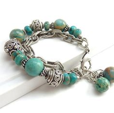 One of my favorite pieces, this turquoise and silver bracelet is made with agate beads that have beautiful markings making each one unique. Silver Bali-style and accent beads give the piece an overall richness. Ive included an antiqued silver chunky chain as part of the design. The bracelet is finished with two turquoise charms and an antiqued silver lobster clasp. This is something youll wear over and over again for any occasion. 7.5 to 8 long and can be adjusted to fit any wrist. ...