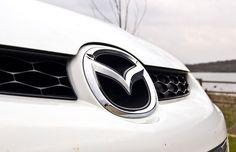 """Logo Mazda - O logo é um M estilizado que parece asas em pleno voo e simbolizam o """"voo ao futuro"""" da Mazda. Segundo a própria empresa, o emblema também se assemelha à abertura de uma hélice, representando criatividade, vitalidade, flexibilidade e paixão. Como um todo, representa a preparação da montadora para abrir suas asas e crescer no século 21."""