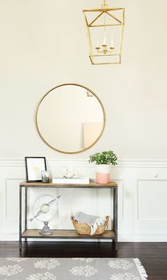 Neutral entry with round mirror and brass lantern. Elegant space from Studio McGee.