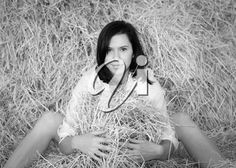 iPHOTOS.com - Portrait of a beautiful girl on a haystack. Toned image
