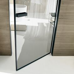 two-directional swing opening, jamb in black aluminium, panel in transparent grey glass and black aluminium section.