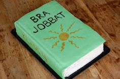 """Book cake with a sun on top. The text says """"good job"""" in Swedish"""