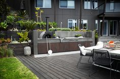 Outdoor kitchen: wood-fire pizza oven, barbecue grill and sink, hand-cut and polished bluestone splashback and benchtop. The cupboard doors are made of cedar, stained to complement the decking.
