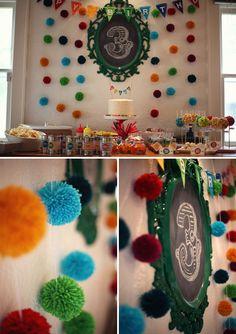 Background: handmade yarn pom-pom balls in a rainbow of vibrant colors,