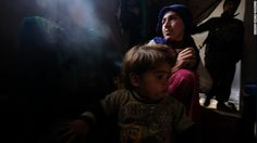 """Zehra, a 25-year-old Kurdish woman who lost her 8-month-old daughter due to a lung infection at a refugee camp, sits with her other daughter inside their home in Kobani, Syria, on Thursday, January 29. Her husband, a fighter from the People's Protection Units, or YPG, stands in the background. After four months of intense fighting, Kurdish Peshmerga forces <a href=""""http://www.cnn.com/2015/02/04/middleeast/kobani-syria-destruction/index.html"""" target=""""_blank"""">have liberated Kobani</a> from the…"""