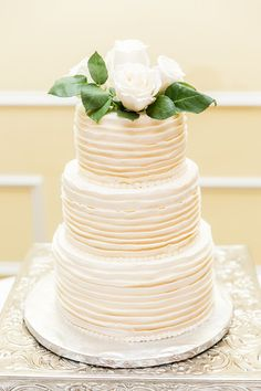 A white three-tiered fondant-frosted wedding cake. Gorgeous! {@RMphotographyNC}