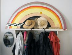 """Our coat rack and hat stash. I painted the rainbow a long time ago for a rejected display prototype."""