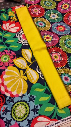 Navy Blue w/ Big Bright Reds, Yellows, Greens Florals w/ Solid Sunny Yellow, and 3rd fabric is same colors with a circlular mod pattern.