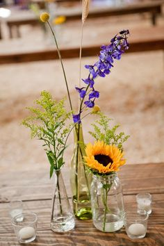Centerpieces don't have to be elaborate to be beautiful. In a natural setting, simple glass vases and a few flowers can do the trick!