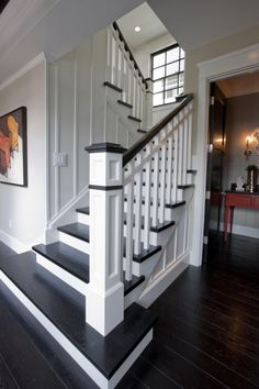 Replace carpet with dark wood floors and paint railing black.