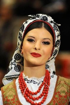 A Polish folk singer wears a head cover with embroidery typical of the town of Hrubieszów in Eastern Poland. She also wears traditional red beads found in many folk costumes through out Poland and the rest of the Slavic world. Red was the colour associated with beauty and elegance to the ancient Slavs. Even in modern times the Russian word for beautiful is homonymous with the word for red.