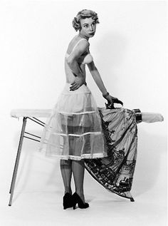 Black and white pin-up of a scantily clad woman ironing her dress