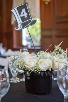 Having a black tie wedding?  This top hat centerpiece with white roses and baby's breath provides a great focal point and helps guests find their seats.  ----------------------Photo courtesy of Helen John Photography