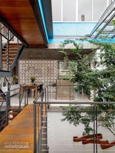 Sem bloquear luz e ventilação naturais, o trecho de cobogós (tijolarte) da fachada não expõe a cozinha (SCA) para a rua. Portas de correr envidraçadas (J&J Esquadrias) vedam o paredão vazado quando necessário. Projeto de Maurício Takahashi.