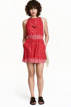 Combi-short à motif: H&M LOVES COACHELLA. Combi-short en tissu de viscose avec motif imprimé. Modèle sans manches avec lien de serrage à l'encolure, à nouer dans le dos. Ouverture dans le dos et découpe élastique à la taille. Poches latérales et jambes amples.