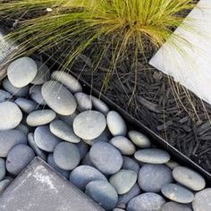 River rock edging between mulch and concrete.