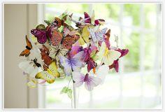 """Dit is een DIY boeket van vlinders (gemaakt van veren). Deze koop je in verschillende kleuren en grootte, bij bijv. droomdecor.nl. Vervolgens voeg je ze samen tot een boeket en buig je de vlinders in de richting dat je ze wilt hebben. Plak vervolgens de """"stelen"""" bij elkaar met wit tape en afwerken met een mooi lint."""