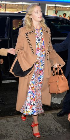 Emily Blunt made a camel coat pop by pairing it with a colorful floral dress by Prabal Gurung. Red sandals made the bright outfit even better.