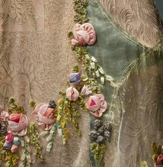 Boué Soeurs (French, active 1899–1957). Court Presentation Ensemble(detail), 1928, Haute Couture. Hand–sewn ivory silk tulle, machine–embroidered with couched silver cord in a foliate and vermicelli pattern; insets of silver–blue silk and metal lamé with machine–picot edging; hand–appliquéd with hand–embroidered white silk tulle with artificial flowers in pink, purple, green, yellow, and blue silk ribbon and floss. Photo © Nicholas Alan Cope. #ManusxMachina #CostumeInstitute