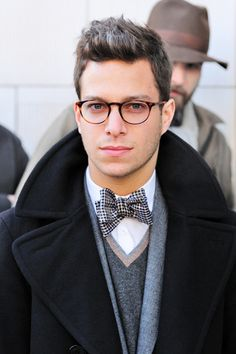 Men's Fall/Winter Fashion, Preppy Style in Navy Wool Overcoat, Sweater, Scarf, Bow Tie, and Round Horn Glasses.