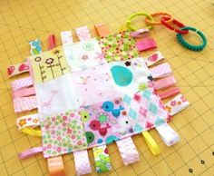 Karen from Sew Much 2 Luv shares a tutorial on her blog showing how to make a baby's taggie toy. The top is made with a colorful patchwork, and ribbon tags in a variety of prints and texture…