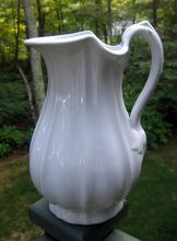 19th Century English White Ironstone Large Ewer / Pitcher    Kansas Shape    J & G Meakin England.    This white ironstone pitcher has a lovely melon ribbed shape ending in a gently scalloped base and a distinctive shaped top. There is an embossed leaf pattern at both the top and base of the handle.    Back stamp is shown and dates this pitcher to c.1850.