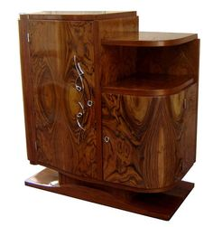 """This asymmetrical French art deco cabinet dates from the 1930s and is constructed of matched Brazilian rosewood veneers and mahogany. The bright nickel fittings contrast with the warm tones of the exotically figured rosewood. Set on a plinth and lap feet, the cabinet features a full door on the left which opens to reveal shelves. The curved door on the right below the shelf covers a storage space. Finished in a high gloss lacquer, the cabinet is 36"""" tall, 31-1/2"""" wide and 16-1/2"""" deep."""